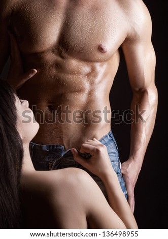 Young woman undressing muscular man on dark background