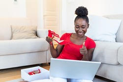 Young woman unpacking parcels with footwear, feeling happy with new online purchases, sitting on the floor at home and face timing her friends to show them her new shoes
