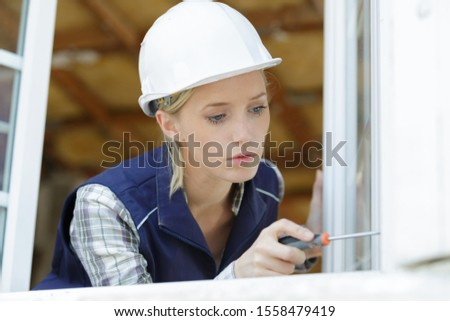 young woman unscrews the fixing screws of the window handle