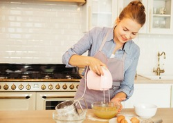 Young woman uses mixer in beating eggs, stands in a modern kitchen