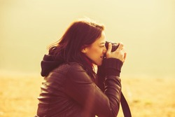 young woman using a camera to take photo outdoors retro colors