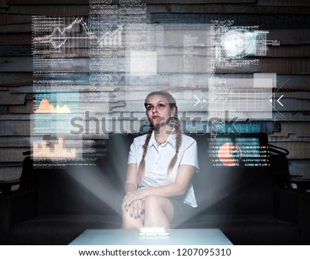 Young woman using a hologram infograph screen at home.Futuristic user interface. #1207095310