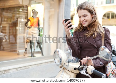 Young woman using a smartphone while standing by her motorbike in the shopping district of a city, with a fashion store window with manikins in the background.