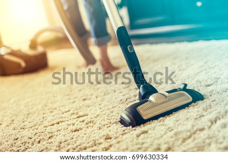 Young woman using a vacuum cleaner while cleaning carpet in the house. - Shutterstock ID 699630334