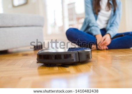 Young woman using automatic vacuum cleaner to clean the floor, controling machine housework robot #1410482438