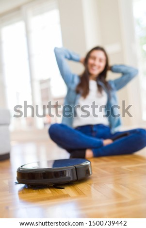Young woman using automatic vacuum cleaner to clean the floor, controling machine housework robot #1500739442