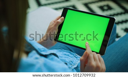 Young woman using black tablet device with green screen. Woman holding tablet, scrolling pages while sitting on the couch in the living room. Chroma key. View over shoulder. Close up