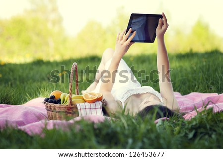 Young woman using digital tablet on meadow