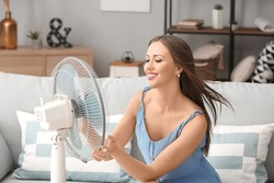 Young woman using electric fan during heatwave at home