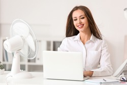 Young woman using electric fan during heatwave in office