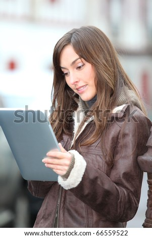 Young woman using electronic pad in town
