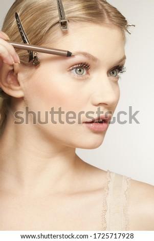 Young woman using eyebrow pencil