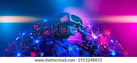 Young woman using glasses of virtual reality on dark background. Smartphone using with VR headset,virtual reality,future technology concept.Asian woman using VR glasses in colorful neon lights.