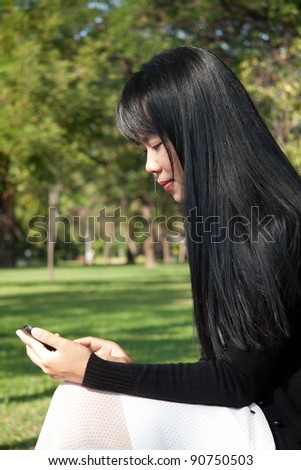 Young woman using handheld in the park.