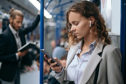young woman using her smartphone on subway train.