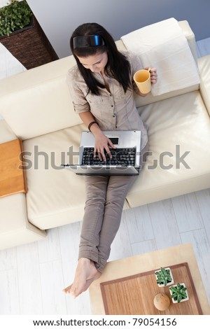 Young woman using laptop at home, sitting on sofa. View from above.?