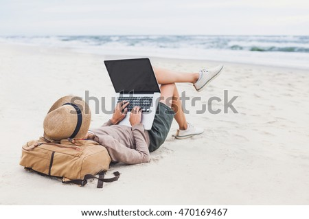 Young woman using laptop computer on a beach. Freelance work concept #470169467