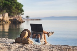 Young woman using laptop computer on a beach. Girl freelancer working by a sea. Freelance work, travel, vacations, stay connected, communication, studying online, e-learning concept