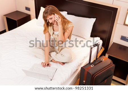 Young woman using laptop in a hotel bedroom