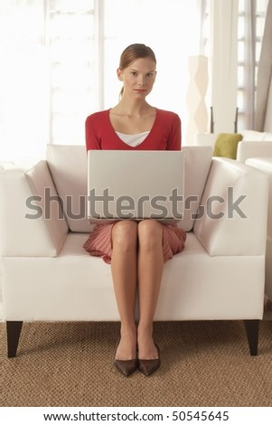Young woman using laptop in living room, portrait