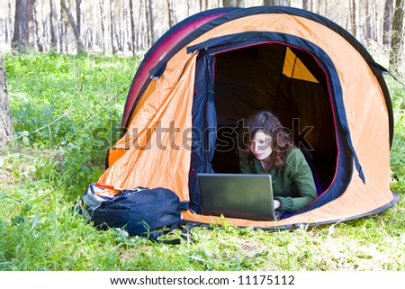 Young woman using laptop in the middle of the forest