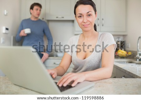 Young woman using laptop with man drinking coffee in kitchen
