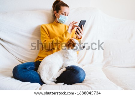 young woman using mobile phone, cute small dog besides. Sitting on the couch, wearing protective mask. Stay home concept during coronavirus covid-2019