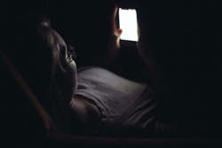 Young woman using mobile phone in dark room at home