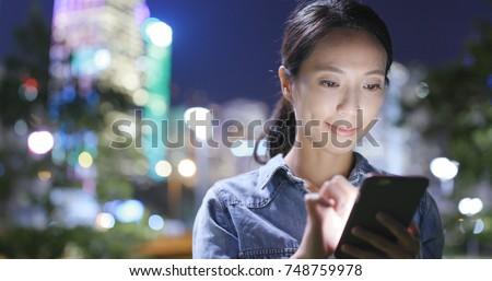 Young woman using mobile phone in Hong Kong city at night