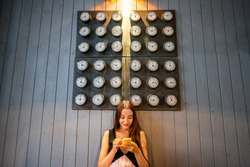 Young woman using mobile phone with many clocks on the wall background. Time phone application concept
