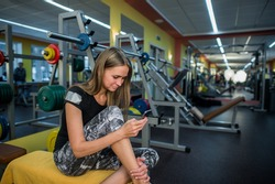Young woman using phone in gym.