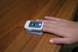 Young woman using pulse oximeter to measure oxygen saturation in covid19 pandemic disease,medical home monitoring treatment