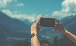 Young woman using smart phone camera for making picture of Swiss Alps. Female traveler blogger taking photos on mobile phone during summer journey vacations.