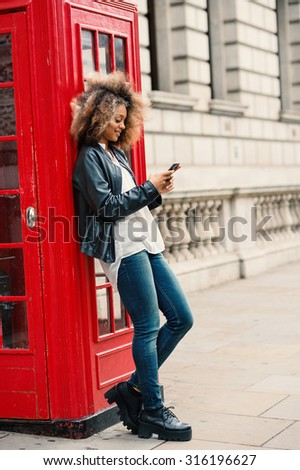 Young woman using smart phone close to red telephone box in London. Full body portrait.
