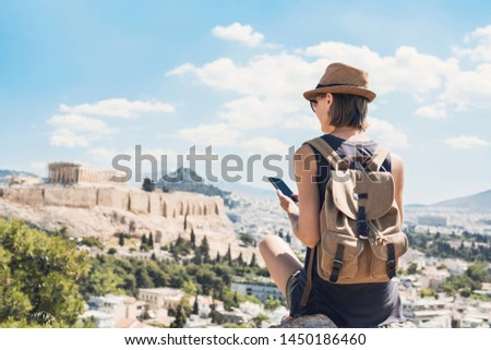 Young woman using smart phone in Athens with Acropolis at the background. Traveler girl enjoying vacation in Greece. Summer holidays, vacations, travel, tourism, technology concept. #1450186460