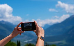 Young woman using smartphone camera for making picture of Swiss Alps. Female traveler blogger taking photos on mobile phone during summer journey vacations.