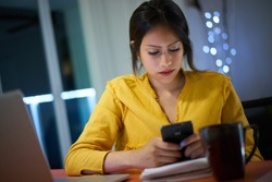 Young woman using smartphone while doing homework at night. Female college student studying and texting with mobile telephone at home.