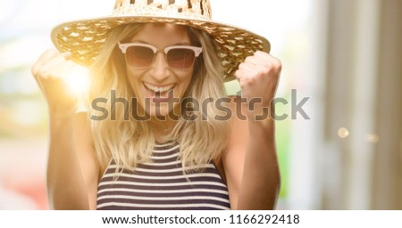 Young woman using sunglasses wearing summer hat happy and excited celebrating victory expressing big success, power, energy and positive emotions. Celebrates new job joyful