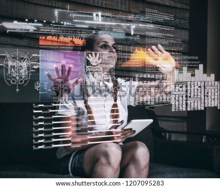 Young woman using tablet and infograph screen at home.Futuristic user interface. #1207095283