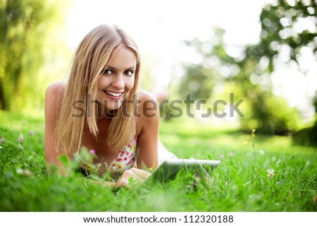 Young woman using tablet outdoor laying on grass, smiling.