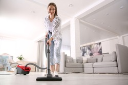 Young woman using vacuum cleaner at home