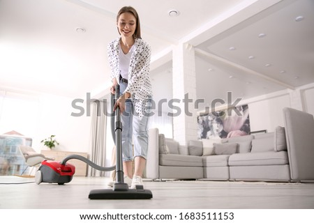 Young woman using vacuum cleaner at home Stockfoto ©