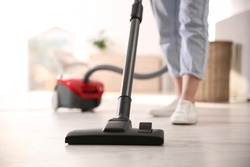 Young woman using vacuum cleaner at home, closeup