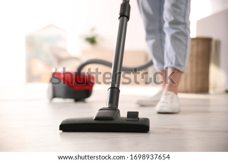 Young woman using vacuum cleaner at home, closeup Stockfoto ©