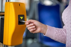 Young woman validates ticket in a public transport during transportation, transportation concept