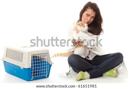 young woman vet stroking cat, transporter in background