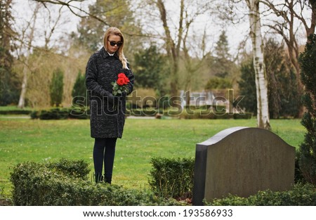 Young woman visiting a loved one at the cemetery paying respects with fresh rose flowers Female grieving at graveyard