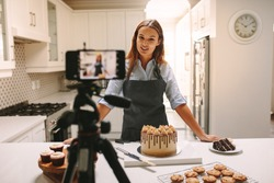 Young woman vlogger baking and recording video for food channel. Female pastry chef vlogging with her mobile phone mounted on a tripod in kitchen.