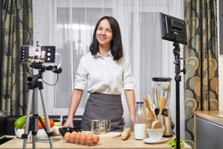 Young woman vlogger recording video for food channel. Female culinary specialist vlogging with her mobile phone mounted on a tripod and ? light stand in kitchen.