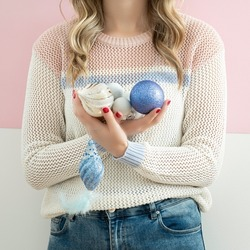Young woman waering white sweater and holding Christmas baubles on white and pink background. Minimal holiday concept.